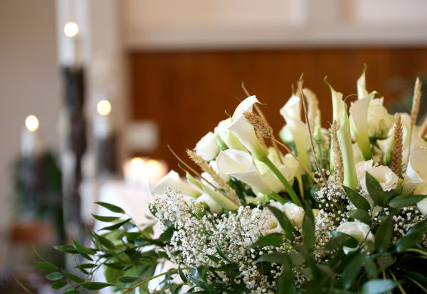 photo of vase of flowers on an altar in the church and the candles on background